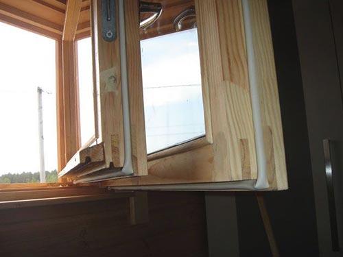 На фото установка деревянных окон со стеклопакетами