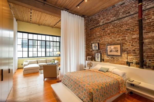 Часто основной акцент делают на стену в изголовье кровати. Ее оставляют без отделки или выделяют искусственным камнем