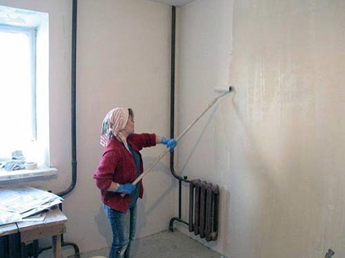 На фото показана грунтовка стен перед поклейкой обоев