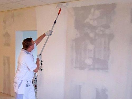На фото показано как наносить грунтовку на стены
