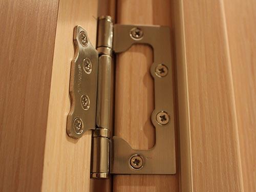 На фото регулировка петель межкомнатных дверей