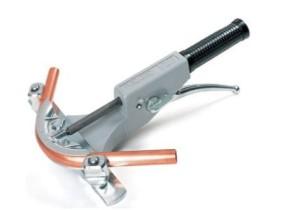 Труба зажимается между упорами, а приходящий в движение от привода упорный башмак гнёт трубу