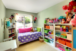 Girls bedroom with many toys and purple bed.